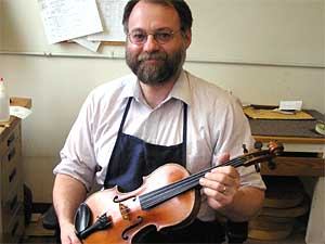 Shop manager Douglas Lay repairs violins played by musicians, music teachers and students.  He began repairing instruments more than 20 years ago.