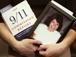 Carie Lemack holds a portrait of her mother Judy Larocque, a victim of the September 11, 2001 attack on the World Trade Center, along with a copy of the 9-11 Commission Report.