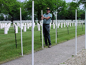 Steve Johnson, a Ft. Snelling cemetery worker, makes sure each pole is straight.  The poles will hold flags for Memorial Day.