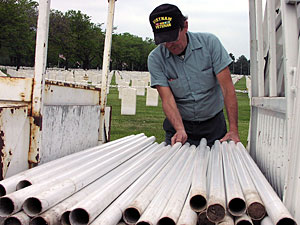 Steve Johnson, Ft. Snelling Cemetery worker picks out the poles that will hold Memorial Day flags.