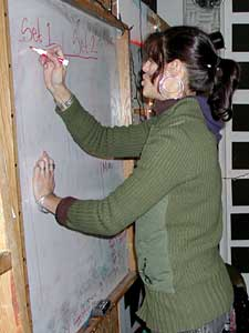 Dessa writes out the band's set list on a whiteboard.