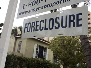 A foreclosure sign hangs in front of a home.