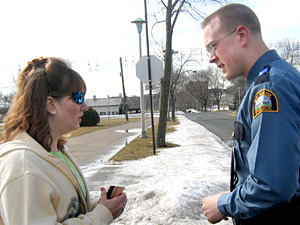 Recruit Charlie Anderson speaks with a female passenger during a traffic stop.