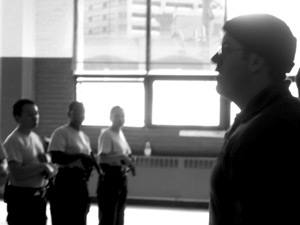 Recruits stand at attention in front of Sgt. Joshua Lego, right.
