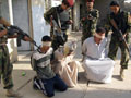 Iraqi soldiers guard blindfolded suspects