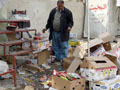 An Iraqi man inspects the damage to his shop.