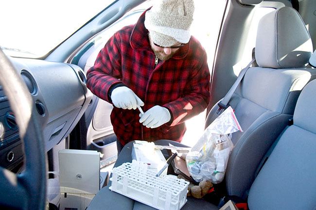 Fond du Lac wildlife biologist Mike Schrage collects serum from a centrifuge loaded with moose blood in the front seat of his truck in the Superior National Forest. The serum is used to determine the health of the animal and determine whether it was exposed to disease.