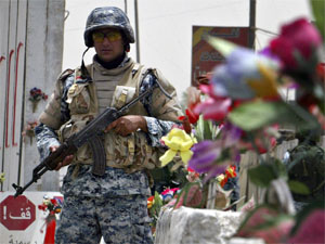 An Iraqi policeman stands guard at a checkpoint decorated with plastic flowers on Palestine street in Baghdad.