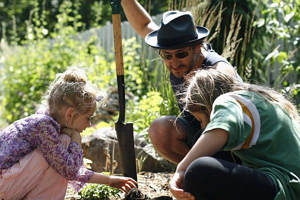 Adam Levy and his daughters, Ava Bella and Esther, dig in their backyard for worms to feed to their chickens.