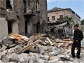 A Georgian man stands among ruins