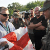 A Georgian journalist offers a flag to soldier