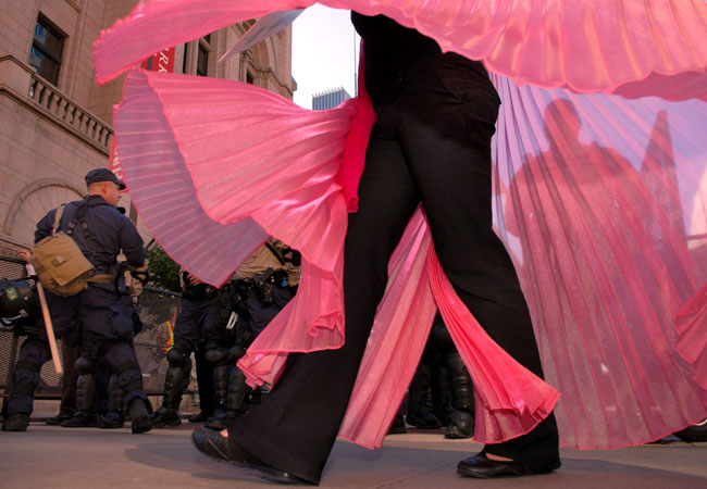 A woman from the Code Pink protest organization swirled her skirt as she danced in front of a phalanx of police blocking an entrance to the Xcel Center.  Four members of the women's peace group were later arrested.