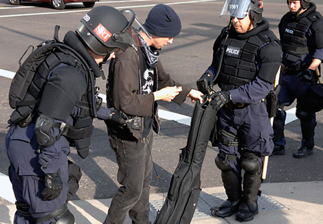 St. Paul Police in riot gear were detaining musicians carrying guitar cases near the McNally Smith Music School. Nate Chamber, 22, of St. Paul hands over his bass guitar to the police.