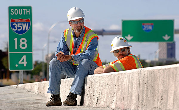Workers from the Flatiron construction company rest on a guardrail and watch Monday morning's press conference.