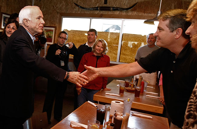 Republican presidential nominee Sen. John McCain (R-AZ) (L) greets local small business leaders, including Russell Duker (R) during a meeting at the Buckingham Smokehouse Bar-B-Q October 20, 2008 in Columbia, Missouri.