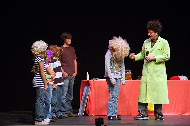 Audience members wearing wigs laugh while participating in Zaloom's live science show.
