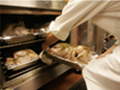 A chef places fresh turkeys in the oven