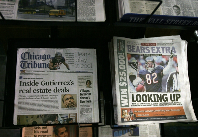 Newspapers are displayed on racks as the Tribune Co., publisher of the Chicago Tribune and Los Angeles Times, sought bankruptcy court protection from creditors December 8, 2008 in Chicago, Illinois. The 161-year-old newspaper and broadcast company was laboring under $12.9 billion in debt, according to today's Chapter 11 filing in U.S. Bankruptcy Court in Wilmington, Delaware. (Photo by Tasos Katopodis/Getty Images)