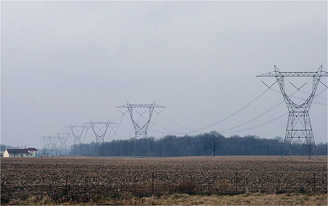 This photo gives a sense of the scale of 765 kV power lines in comparison to a home (far left).