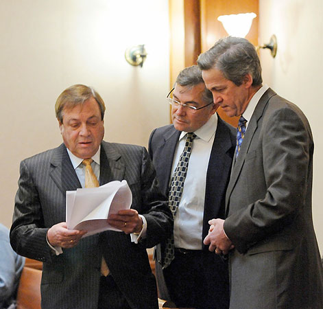 Republican Norm Coleman, right, looks on as his attorneys, Joe Friedberg, left, and Tony Trimble read a court order during a court delay before the start of the Senate vote recount trial Thursday, Feb. 26, 2009, in St. Paul, Minn.