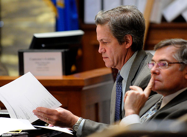 Former Republican Sen. Norm Coleman looks at a paper during the Senate vote recount trial.  At right is attorney Tony Trimble.