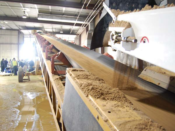 A conveyor belt moves sand as volunteers help to fill sandbags.