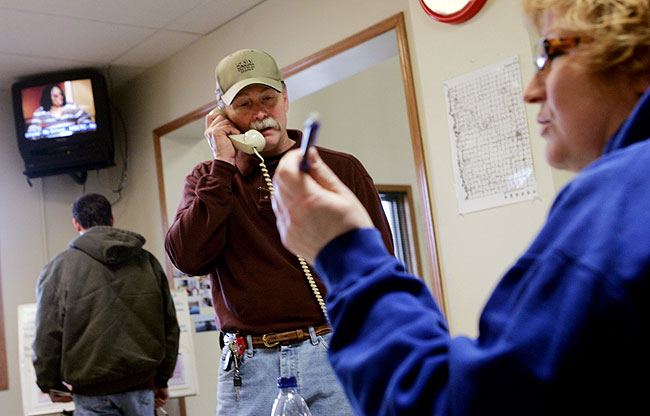 With Ann Zidon conducting personnel, Mike Smart, incident commander in Hendrum, Minnesota, talked on the phone in the town's civic center Monday, March 30, 2009.