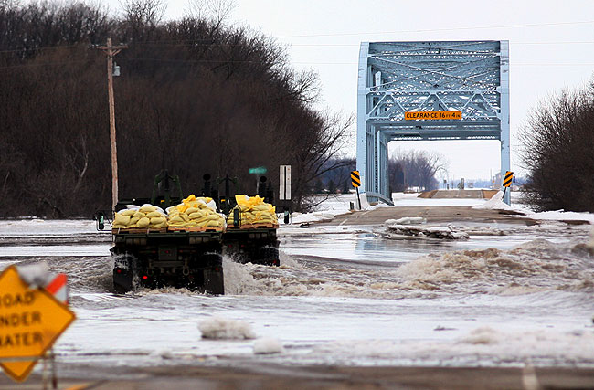 Military vehicles navigated over a flooded road as they delivered sandbags to a nearby farmstead in Hendrum, Minnesota, March 30, 2009.
