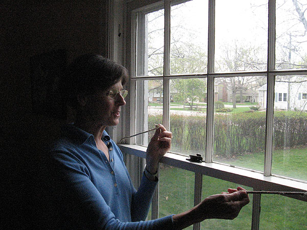 Roseville homeowner Jerry McClelland holds broken sash ropes on a double hung window she's considering replacing.