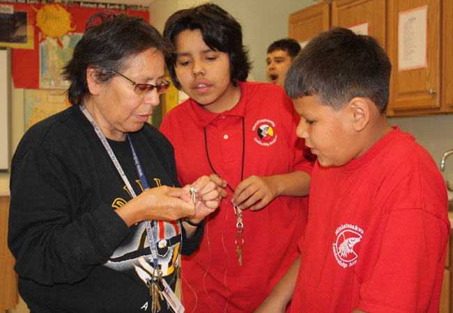 Winnie LaPrairie is the Ojibwe language and culture teacher at the Minisinaakwaang Leadership Academy. She's teaching her students how to bead with porcupine quills. The students are making earrings to sell and raise money for school trips.