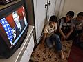 Palestinian boys listen to Obama