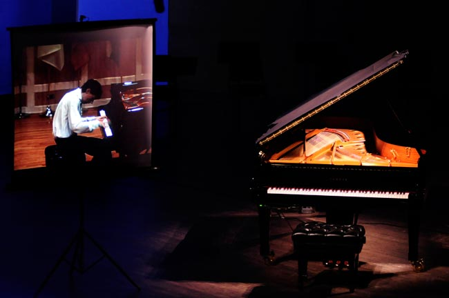 A video of 2008 e-competition pianist Vladimir Levit is played on the screen, while the piano on the stage reproduces the actual recording.