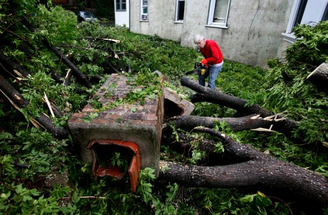 Emmett Winter works to clear a down tree at his Minneapolis property Wednesday, August 19, 2009.