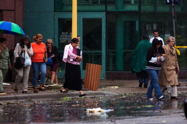 People exit the Convention Center into debris filled streets after severe weather swept through downtown Minneapolis.