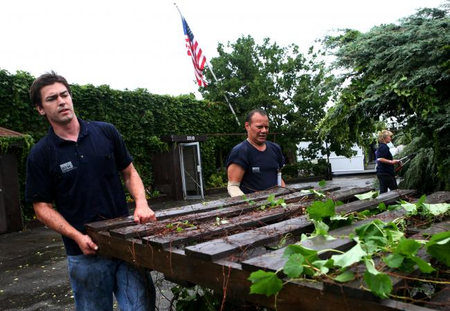 Charlie Fourness, left, and Steve Ramirez move a fence that blew down as severe weather moved through south Minneapolis Wednesday, August 19, 2009.