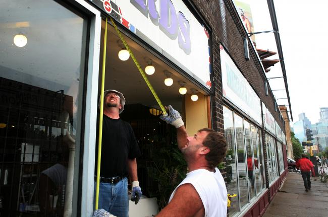 Craig Swanson and Tim Kazynski replace a broken window at the Electric Fetus in Minneapolis Wednesday, August 19, 2009.