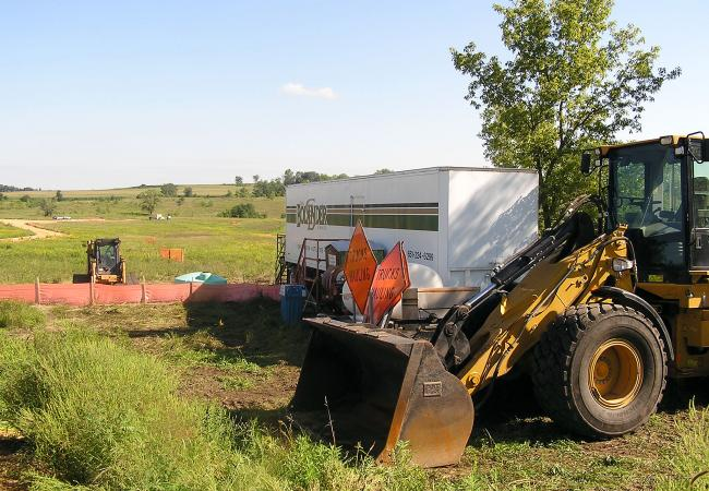Earth-moving equipment stands by at the 3M cleanup site in Woodbury. A contractor will dig up about two acres of soil, eighteen feet deep, and haul it to a specially-prepared section of the SKB Landfill in Rosemount. The soil is contaminated with perfluorinated chemicals produced by 3M until 2002.