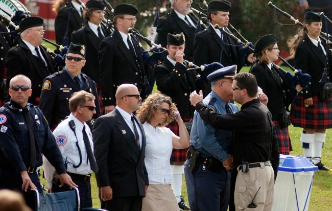 A hug is exchanged before the start of Richard Crittenden's funeral service in Maplewood Friday, September 11, 2009.