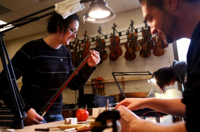 Emily Titus, left, joked with classmate Jonathan Simon, right, as they worked on restringing bows at MInnesota State College - Southeast Technical in Red Wing, Minn. Tuesday, Oct. 13, 2009. The students are part of the Violin Repair Program at the college where they learn about tools, wood, trees, basic principles of repair, and basic maintenance techniques.