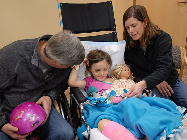 Julia Griggs' mother, Heather, showed off her doll's matching pink cast. Doctors say a ski helmet saved her life. MPR Photo/Tim Nelson