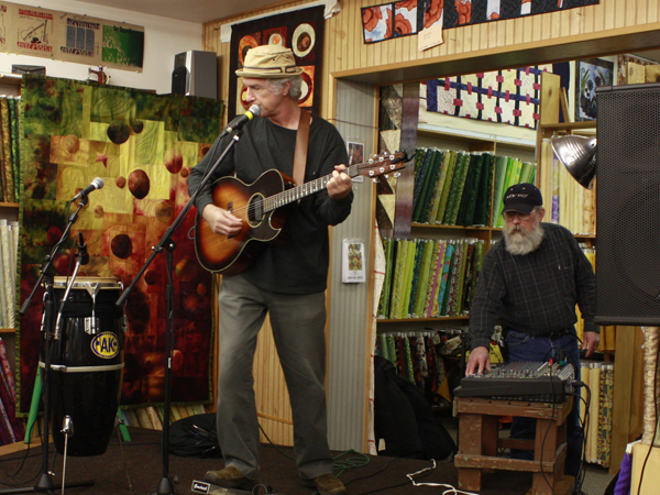 Pete Heitzman stands on a cutting table-turned-stage during a sound check at Aunt Annie's Quilts & Silks shop in Avon, Minn., on Sunday, Oct. 17, 2010. The legs of the table have hinges so that the table easily folds into a stage.