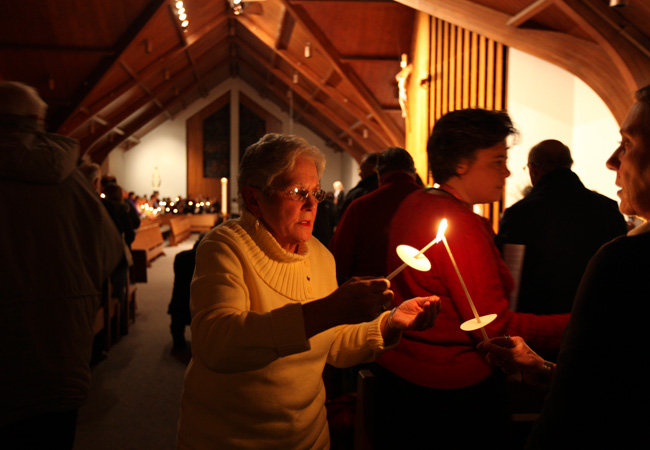Bobbie Driscoll lights candles for people during the prayer service for Jerry and Barbara Heil at the Church of St. Pius X in White Bear Lake Minn., Wednesday, Jan. 18,  2012. The Heils are the only Americans unaccounted for among the more than 4,200 people aboard the Costa Concordia when it struck a reef Friday near Tuscany, Italy.