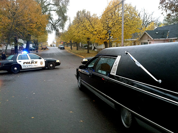 A squad car and a hearse are at the scene of a shooting involving St. Paul Police officers in the Payne-Phalen neighborhood, Tuesday, Oct. 23, 2012.