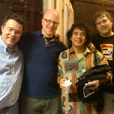 Performance Today host Fred Child with double bassist Edgar Meyer, percussionist Zakir Hussain and banjo player Bela Fleck.