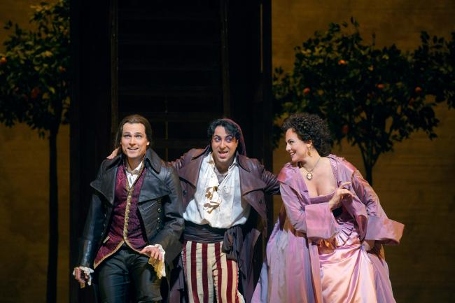 "Alek Shrader as Count Almaviva, Rodion Pogossov as Figaro, and Isabel Leonard as Rosina in Rossini's ""The Barber of Seville."" (Ken Howard/Metropolitan Opera)"