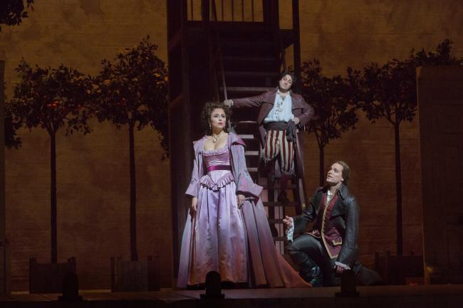 "Isabel Leonard as Rosina, Rodion Pogossov as Figaro, and Alek Shrader as Count Almaviva in Rossini's ""The Barber of Seville."" (Ken Howard/Metropolitan Opera)"