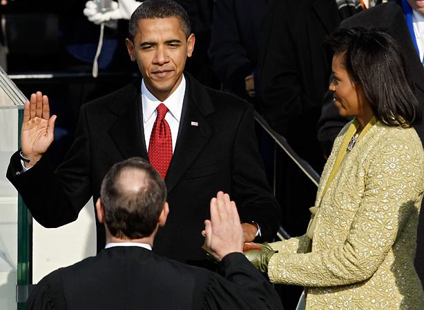 Barack H. Obama is sworn in by Chief Justice John Roberts as the 44th president of the United States on the West Front of the Capitol as his wife Michelle looks on Jan. 20, 2009 in Washington, DC.