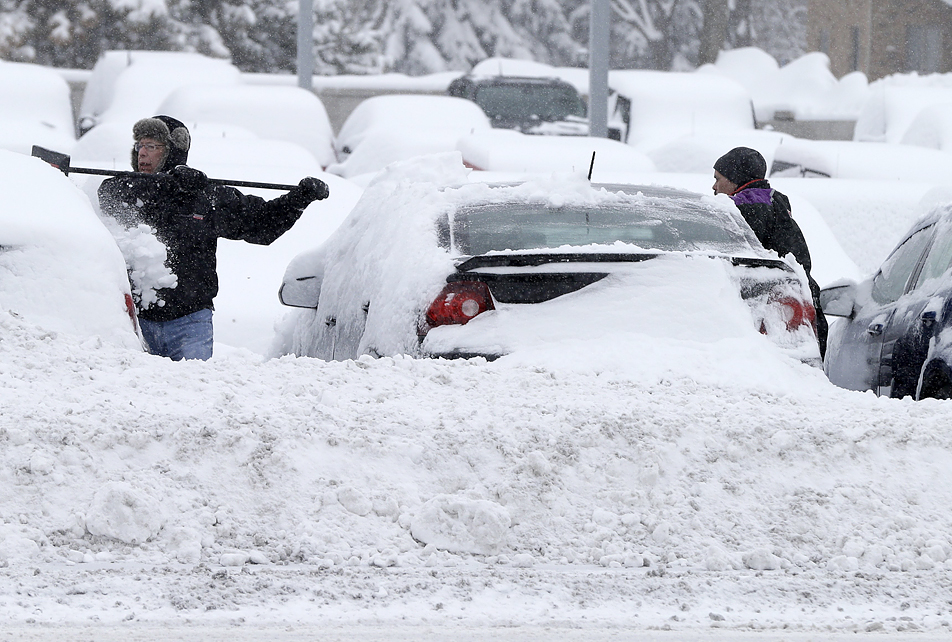 Workers remove snow at an auto dealership