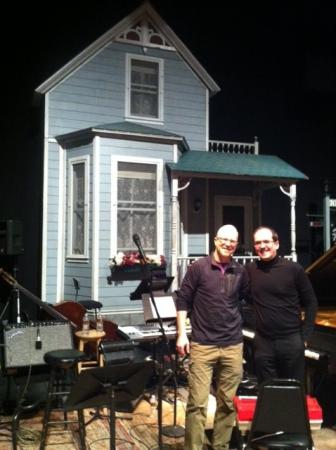 Robert Plano and Fred Child, on stage at the Fitzgerald Theater (the set for A Prairie Home Companion is in the background).
