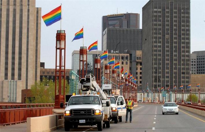 Saint Paul city workers install rainbow flags on the Wabasha street bridge in anticipation of the Minnesota state Senate.